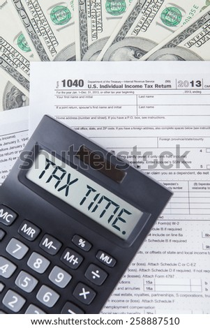 Closeup of tax time word with tax form, dollars cash, symbolizing the time to pay tax - stock photo