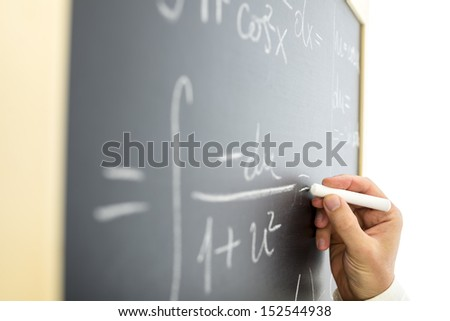 Closeup of teacher writing complicated mathematical equation on black board. - stock photo