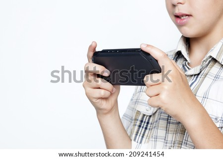Closeup of teen boy playing video games in a portable game console against gray background  - stock photo