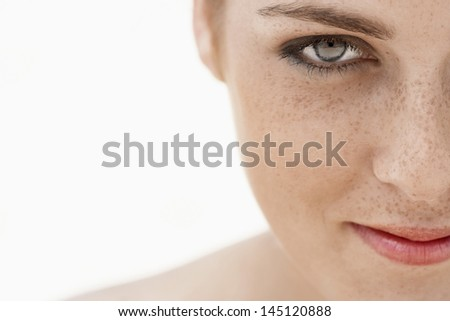 Closeup of teenage girl's face with freckles isolated over white background - stock photo