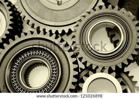 Closeup of teeth of steel gears meshing together - stock photo