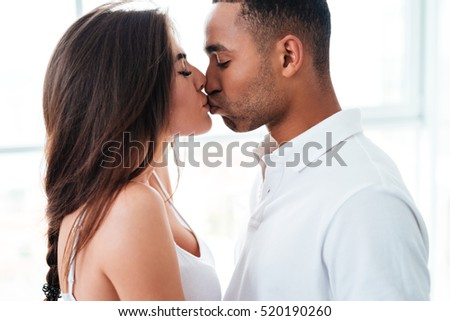 Closeup of tender young couple standing and kissing at home