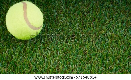 Closeup of tennis ball on green grass background. Selective focus.