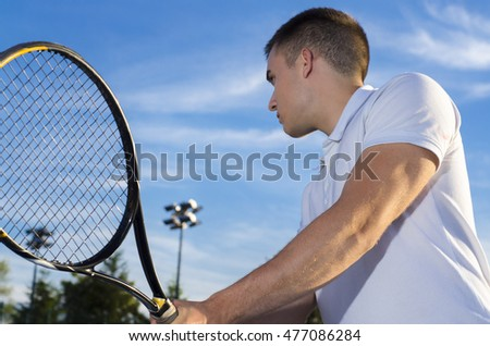 Closeup of tennis player in action, outdoors, blue sky background, selective focus on arm
