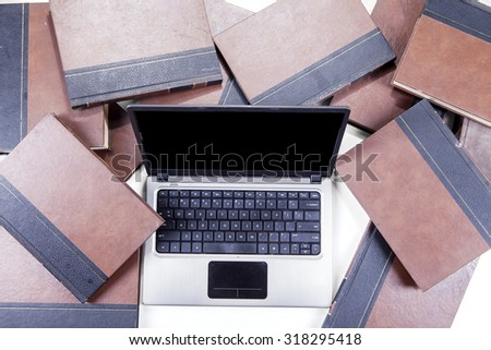 Closeup of textbooks around the laptop computer with blank screen - stock photo