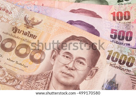 Closeup of Thai banknotes and coins. Thailand paper currency and coins on table. Thai bath with the image of Thai King Bhumibol Adulyadej.