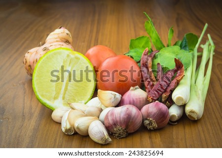 Closeup of Thai ingredients, galangal, lime, lemongrass,tomato,lemon, chilli, garlic and lime leaves - stock photo