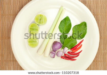 Closeup of Thai ingredients, lime, lemongrass, chili, shallots and lime leaves - stock photo