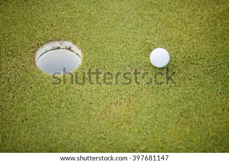 Closeup of the ball near the hole at the golf course