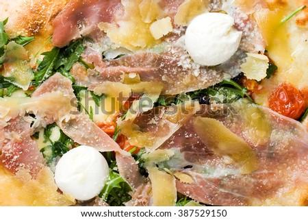 Closeup of the centre of a true Italian pizza with mozzarella, parma ham and tomatoes - stock photo