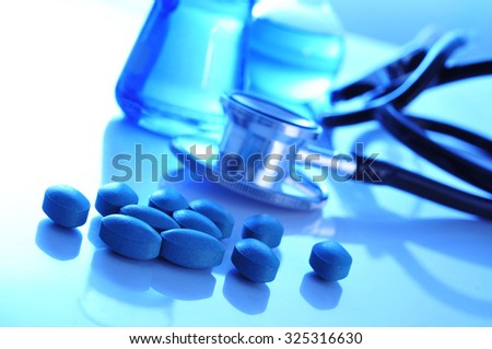 closeup of the desk of a doctors office with pills a stethoscope and some flasks