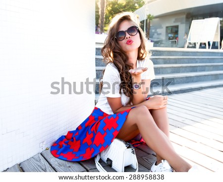 Closeup of the face belong to beautiful young sexy brunette girl with curly hair pure tan glowing skin and bright makeup red lips,red lipstick kiss,long earrings in dark shadows of palm leaves.trendy - stock photo