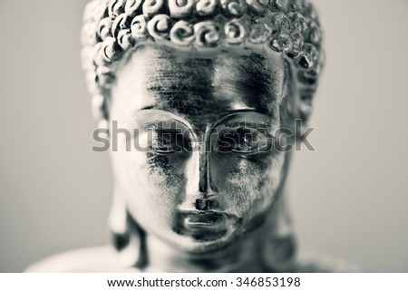 closeup of the face of a representation of the buddha in duotone - stock photo