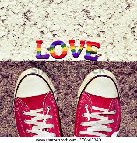 closeup of the feet of a man wearing red sneakers stepping on the asphalt where a pile of letters painted as the rainbow flag form the word love - stock photo