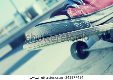 closeup of the feet of someone who is skateboarding in the street - stock photo