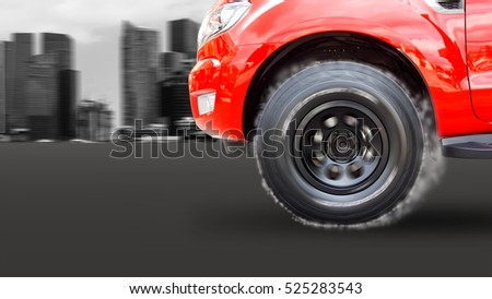 closeup of the front wheels that spin and cause smoke with blurred skyscrapers background