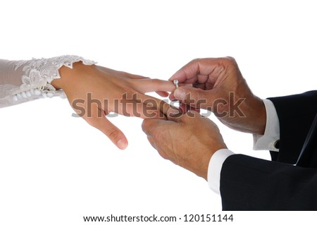 Closeup of the groom placing a wedding ring on the brides hand. Horizontal format over a white background. - stock photo