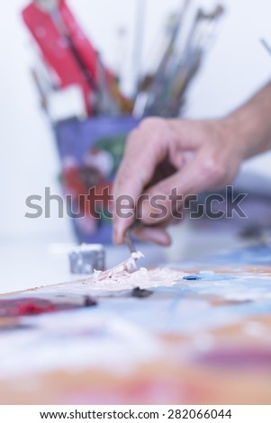 closeup of the hand of a male painter mixing paint with the palette knife over the palette at his painting studio - focus on the palette knife - stock photo