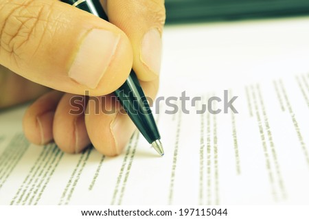 closeup of the hand of a man ready to sign a document with a pen, with a retro filter effect - stock photo