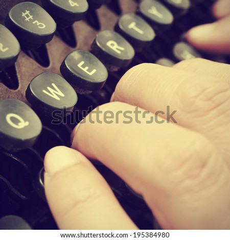 closeup of the hand of a man typing on an old typewriter, with a retro effect - stock photo