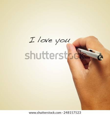 closeup of the hand of a man writing with a pen the sentence I love you on a beige background, with a retro effect