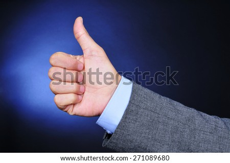 closeup of the hand of a young caucasian businessman wearing a grey suit giving a thumbs-up sign on a black background lightened in blue - stock photo