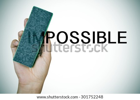 closeup of the hand of a young man deleting the word impossible with an eraser - stock photo