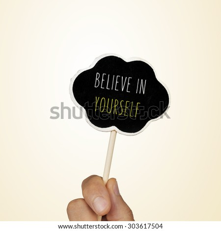 closeup of the hand of a young woman holding a chalkboard in the shape of a thought bubble with the text believe in yourself written in it - stock photo