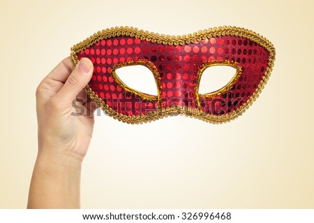 closeup of the hand of a young woman holding a red and golden carnival mask on a beige background - stock photo