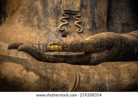 Closeup of the hand of Lord Buddha with gold leaf applied on finger nail. - stock photo