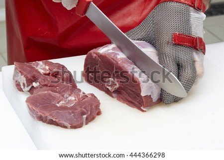 Closeup of the hands of a butcher cutting slices of raw meat off a large loin