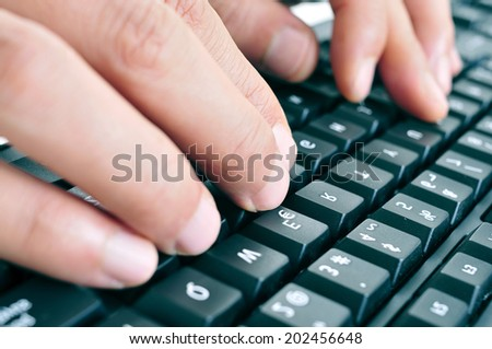 closeup of the hands of a man typing on a computer keyboard - stock photo