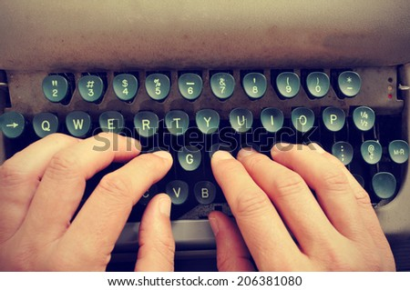 closeup of the hands of a man typing on an old typewriter - stock photo