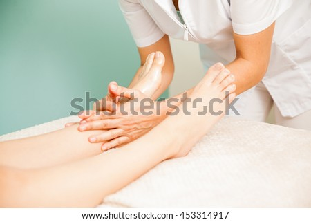 Closeup of the hands of a therapist in the middle of a reflexology session with a client at a health spa