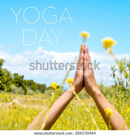closeup of the hands of a young caucasian yogi man meditating outdoors in anjali mudra and the text yoga day - stock photo