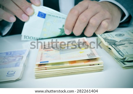 closeup of the hands of a young man who is counting euro banknotes on a table with some pile of pound, euro and dollar banknotes - stock photo