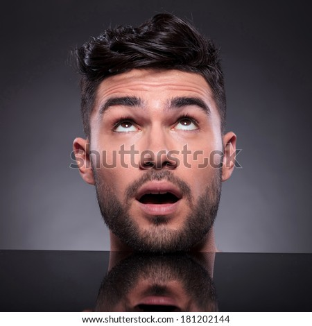 closeup of the head of a young man looking up with his mouth opened. on a black studio backgroud - stock photo