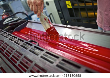 closeup of the ink rollers of a printing press offset machine - stock photo