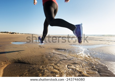 Closeup of the legs of a runner when stepping a puddle on the sand of the beach - stock photo