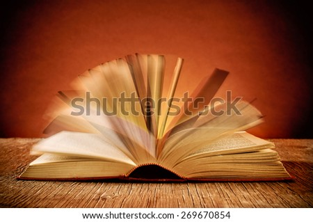 closeup of the pages of an open old book while they are turning, on a rustic wooden table - stock photo