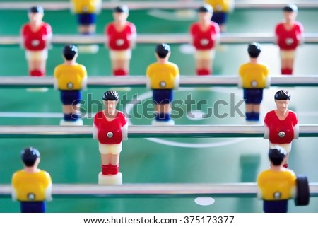 Closeup of the table football or foosball players in red and yellow jerseys.