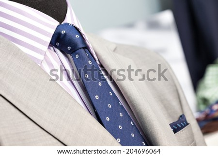 Closeup of the upper section of a grey man suit with striped shirt, grey coat and blue spotted tie in a store or showroom