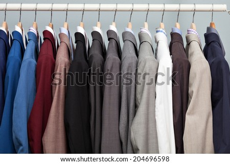 Closeup of the upper section of a row of different coloured man suits in a closet on hangers in a store or showroom - stock photo