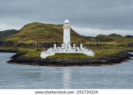 Closeup of the white lighthouse of Lismore between a gray silver sea and sky, near Mull and Oban, in the Hebrides of Scotland. The solid beacon gives guidance, warning, safety to ships near the coast. - stock photo