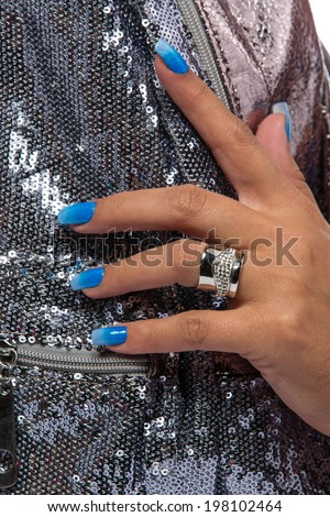 closeup of the woman's hand wearing luxury ring, blue gradient nail art manicure on silver sequin material background  - stock photo