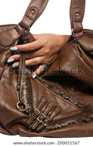 closeup of the woman's hand wearing luxury ring, green pastel mint nail art manicure with brown  leather bag, isolated on white studio background