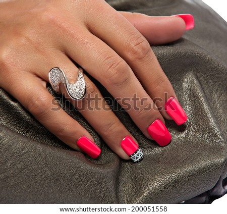 closeup of the woman's hand wearing luxury ring, pink nail art manicure on bronze leather bag background - stock photo