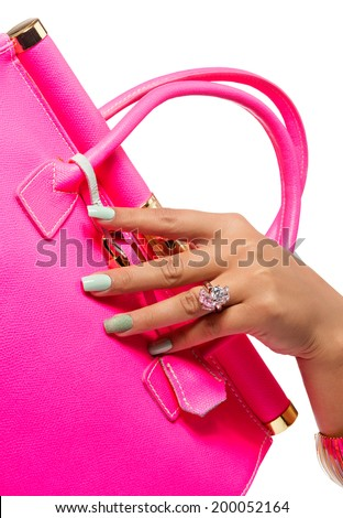 closeup of the woman's hand with mint art manicure, holding pink neon handbag isolated on white studio background - stock photo