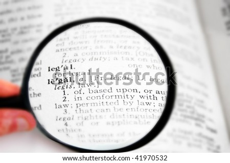 closeup of the word Legal in a dictionary, with magnifying glass - stock photo