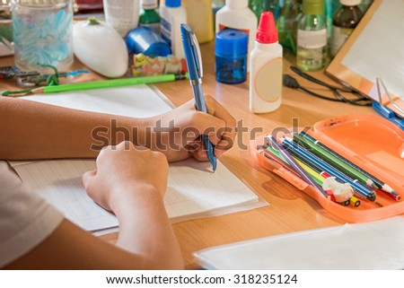 Closeup of the writing school boy hands. Student writind in notebook, homework preparing. Busy kid at home. Writing hand of the school kid rear view. - stock photo